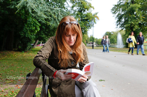 Woman reading in Cannon Hill Park, Edgbaston, Birmingham, West Midlands, England, UK
