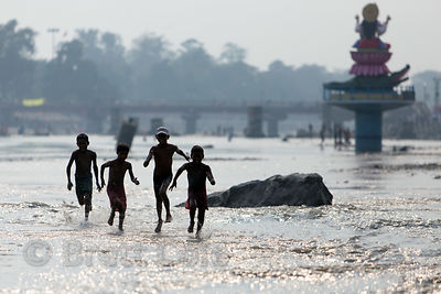 Boys play in the Ganges River near a large statue of Shiva, Haridwar, India