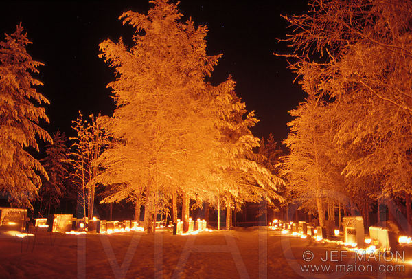 Cemetery lit by Christmas candles at night