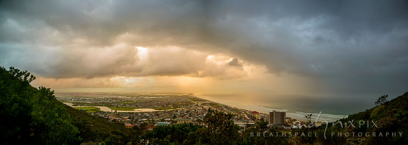 A panoramic view of Muizenberg Village showing the beach, Zandvlei, Marina da Gama and the Cape Flats, rain falling from dark storm clouds over the sea, yellow sunlight illuminating the clouds.