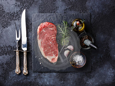 Raw fresh meat steak Striploin, knife and fork carving set and seasonings on dark background