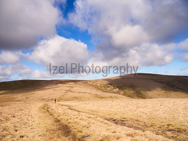 A hiker walking towards Great Lingy and High Pike from the summit of Carrock Fell in the English Lake District, UK.