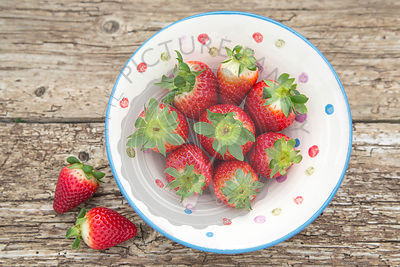 Whole Spanish strawberries in a ceramic rustic bowl, placed on rustic wooden table