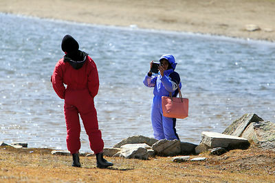 Indian tourists in rented snowsuits take photos at the small lake at Snow Point atop Rohtang Pass (13,054 ft., 3,979 m) in the Pir Panjal range, Manali, India