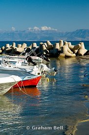 boats moored in new harbour, with the mountains of albania in the distance, san stefanos, north west, corfu, ionian islands, greece.