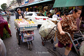 A woman pushes her fruit cart down the streets of a fruit and flower market in Bangkok, Thailand.
