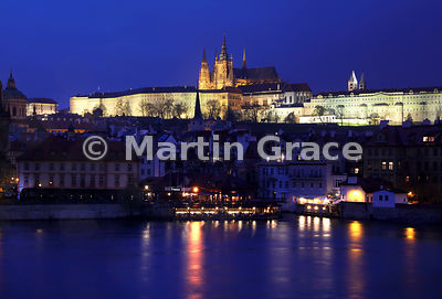 Prague Castle with St Vitus's Cathedral illuminated at night, over the River Vltava from Charles Bridge, Prague, Czech Republic