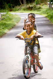 smiling indonesian kids on bicycle