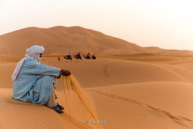 A camelier in the sand dunes of Erg Chebbi in Sahara Desert, Morocco