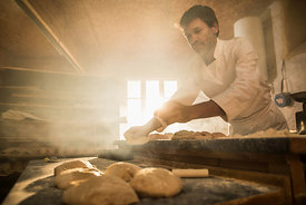 In an artisan bakery, a baker prepare the bread dough. The morning sun comes in through the window...