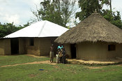 Two mud huts with family outside one with thatched roof and one with tin roof, built with procedes from a charity donated cow, Busia, western, Kenya Africa