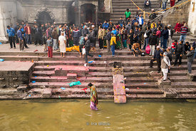 A worshipper walking through the Bagmati River at Pashupatinath Temple in Kathmandu, Nepal.