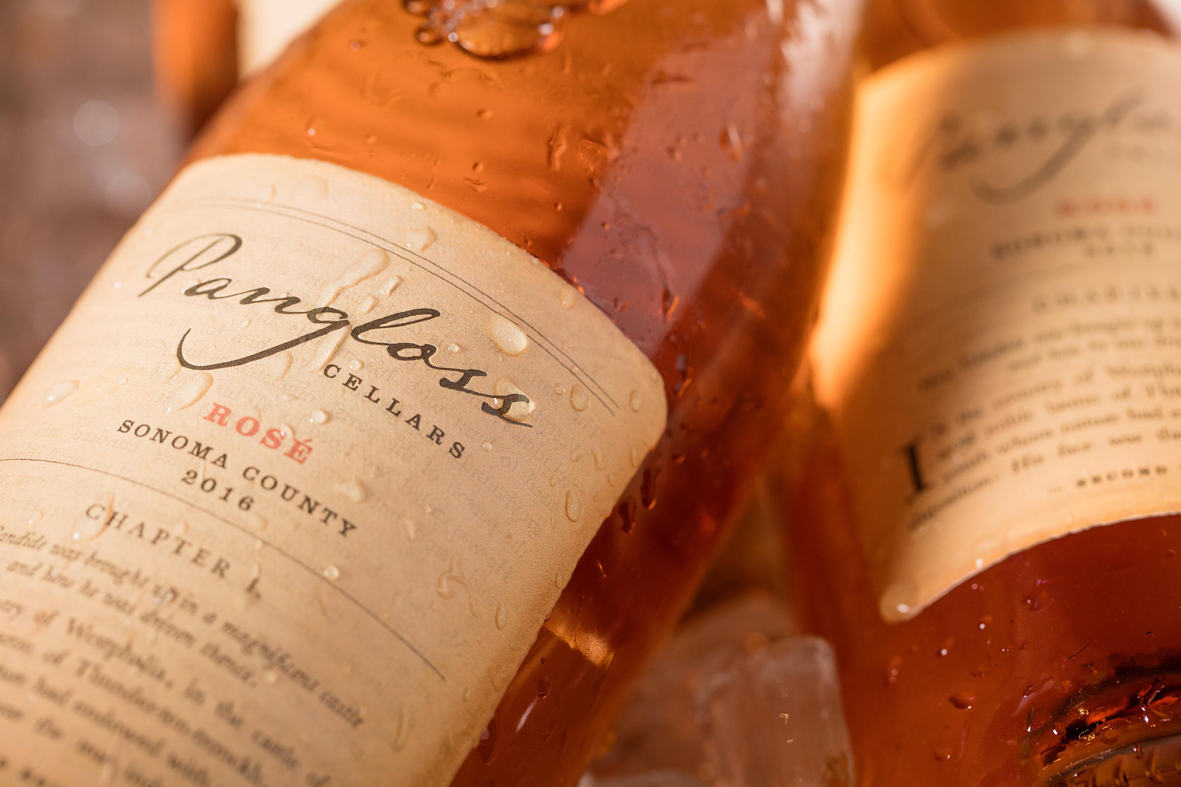 Close up photo of ice cold rosè wine bottle by Jason Tinacci