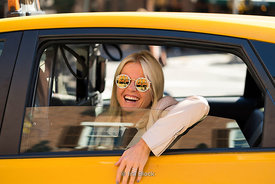 A woman in a yellow taxi in New York City.