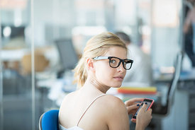Blonde business trainee with her pink phone looking at camera. She is wearing a white top and watches and trendy glasses. She is sitting in a blue chair at a desk in a luminous office
