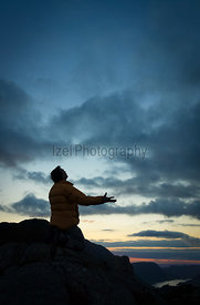 A man pleading to God on the summit of a mountain