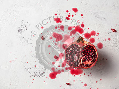 Half pomegranate on a white textured surface with pomegranate juice splashed around.