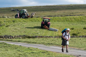 Hiker on the Coast to Coast trail across the North of England passes through a hill farm in North Yorkshire, UK.