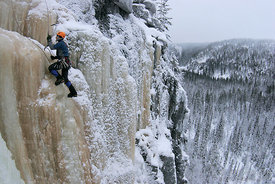 Ice climbing above winter forest landscape
