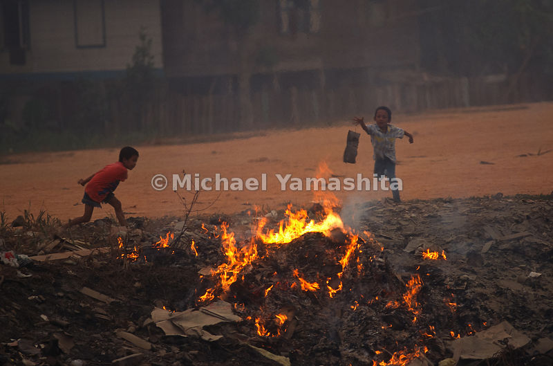 Two boys throw an unwanted item into a fire pit after the devastation of Indonesia's Plague of Fire.