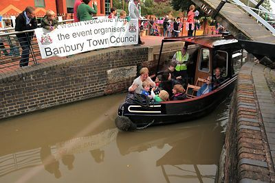 Passengers Pass under Spiceball Lift Bridge by a Banbury Town Council Banner