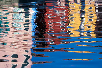 Colorful buildings reflected in the water of a canal.