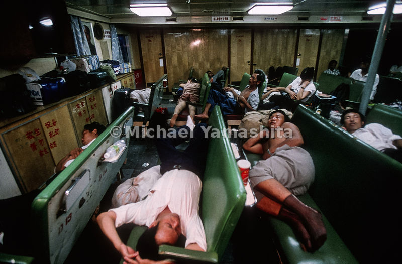 Ferrying between two of China's laboratories of free enterprise - Haikou and Beihai - workers sleep away a 12-hour journey that costs six dollars - three days' pay at minimum wage.  North of Hainan, China.