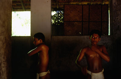 India - Kerala - Boys oils themselves before a massage by his teacher at the Kerala Kalamandalam.