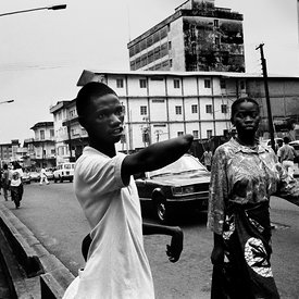 Hassan Fofona begs for money outside the central post office, Freetown. Crippled by polio, rebels hacked off his good arm on a tree stump.