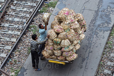 Workers load baskets onto a cart at the Delhi Railway Station, Delhi, India
