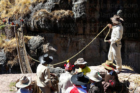 Men pull one of the new foundation ropes across the canyon , Q'eswachaka , Canas province , Peru