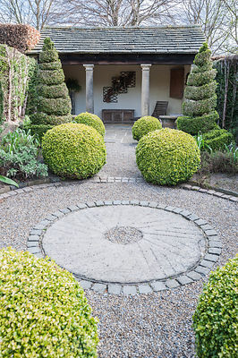The Herb Garden with topiary box and yew shapes, a summerhouse at one end, and a central gravel path edged with stone setts. York Gate Garden, Adel, Leeds, Yorkshire