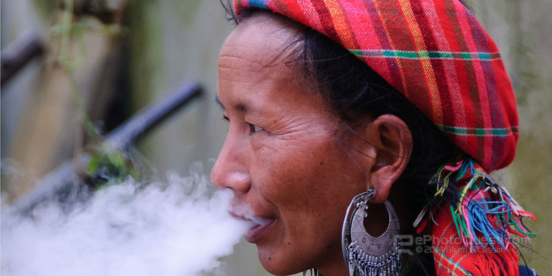 Older Black Hmong Woman Smoking Pipe
