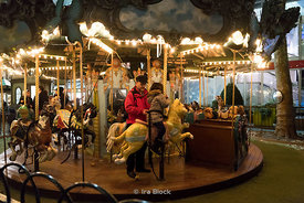 A father and daughter on the carousel at Bryant Park Winter Village in Manhattan, New York