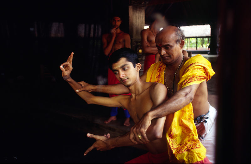 India - Kerala - In a mirror, Professor Balasubramanian, a senior teacher of Kathakali shows a student a difficult step in class at the Kerala Kalamandalam.
