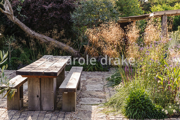 Chunky oak table and benches on a sunny terrace beside the house, with Stipa gigantea, Verbena bonariensis and salvias in adjoining bed. The 'Garten' Garden, Lower Treculliacks Farm, Falmouth, Cornwall, UK