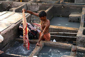 A washerman (dhobi) cleaning a piece of clothing at Dhobi Ghat, a laundry district in Mumbai, India.