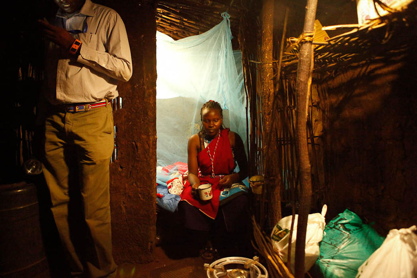 A Masai couple use a solar lamp in their remote village of Eremet, northern Kenya. The Matonyok Nomads Development Organisation (MANDO) introduced 45 of these lamps into the village in April 2012.