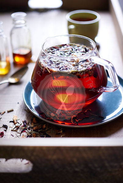 A bright airy scene of a warm wood tea tray with loose leaf tea floating in red tea in a glass teapot with honey and mug in background.