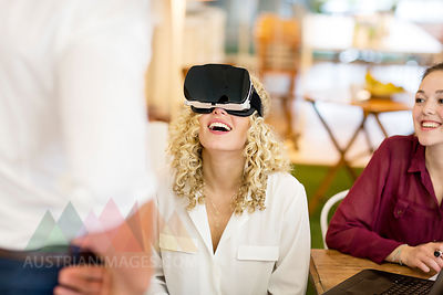 Blond woman trying out VR goggles at a workshop