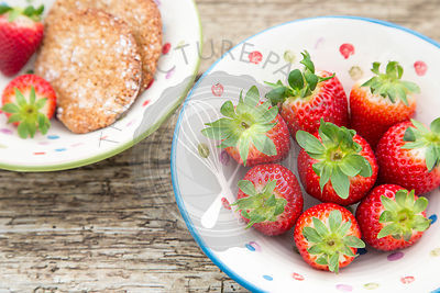 Whole Spanish strawberries in a ceramic rustic bowl, placed on rustic wooden table with homemade hazelnut cookies.