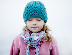 Portrait of a little girl in a pink shirt and blue hat