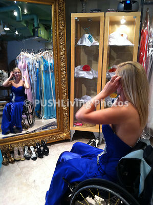 Young woman using a wheelchair trying on a new dress