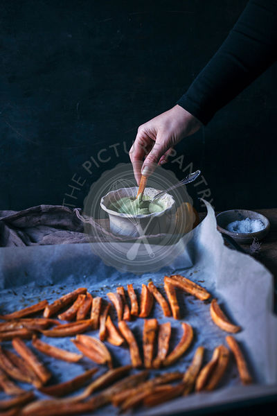 Woman dipping oven baked sweet potatoe fries into avocado sauce