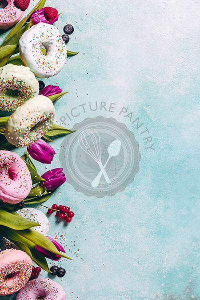 Sweet and colourful doughnuts with sprinkles, purple tulips and berries falling or flying in motion against blue pastel background. Border with space for text