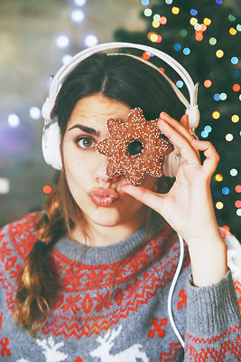 Woman with headphones looking through a Christmas cookie