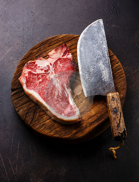 Raw fresh meat Dry Aging Steak T-bone and Butcher cleaver on cutting board on dark background