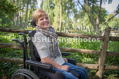 Happy  girl with a disability in a wheelchair in an urban park