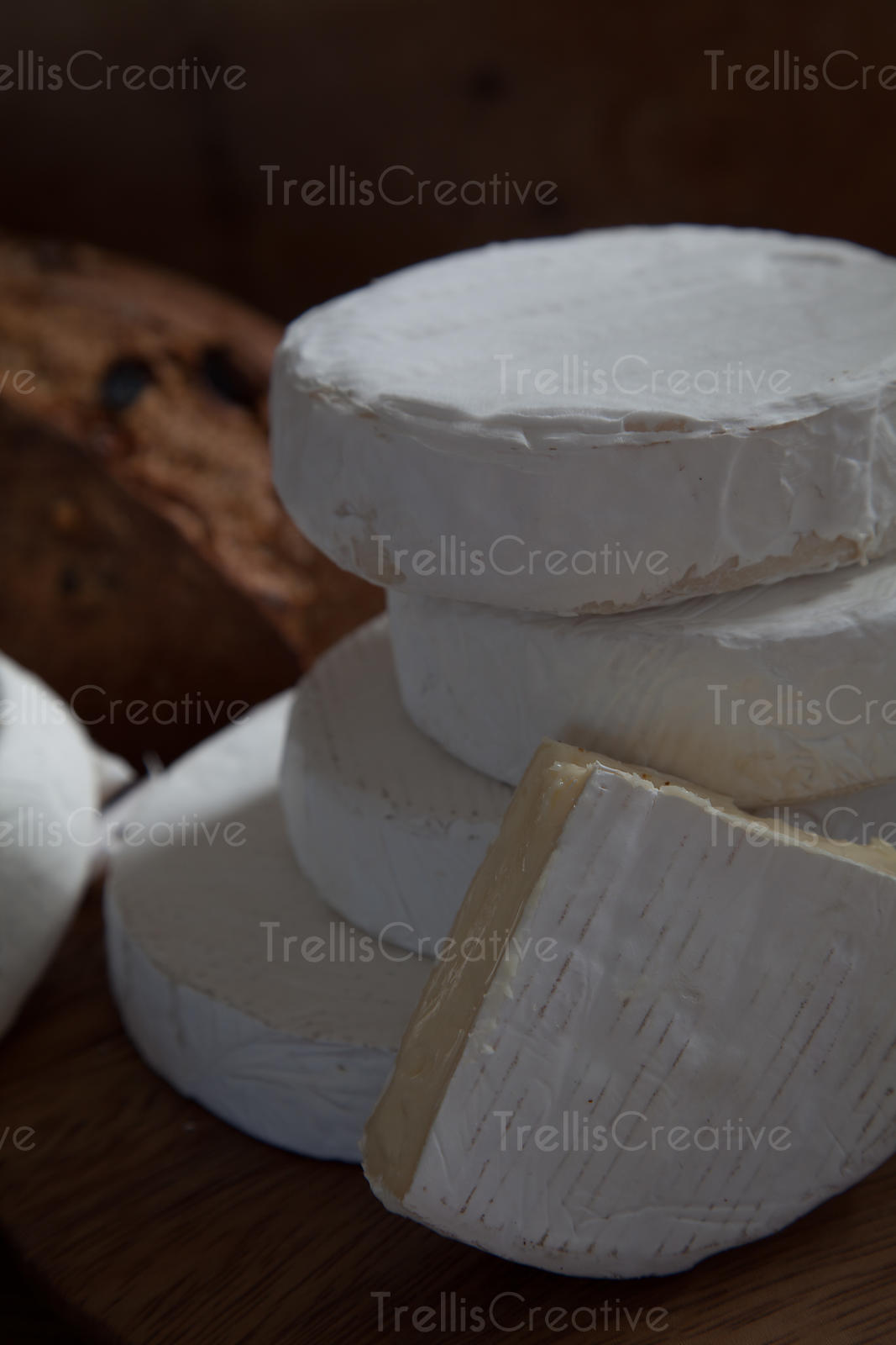 Stacks of camembert brie wheels with a cheese wedge, close-up