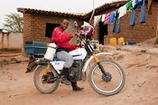 Rural vet on motorcycle, carrying AI flask and vet supplies. Rwanda